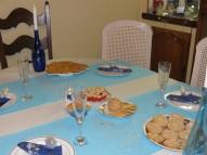 Sur la table, une nappe blanche surmontée de chemins de table bleu ciel avec quelques paillettes au centre